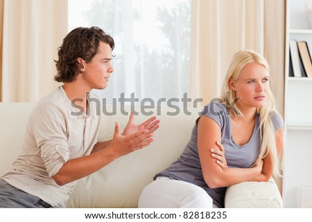 Young couple arguing in their living room - stock photo