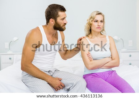 Young couple arguing on bed in bedroom
