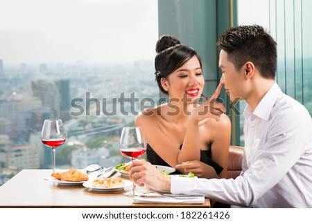 Young couple at a date, attractive woman touching her man'??s nose with a finger