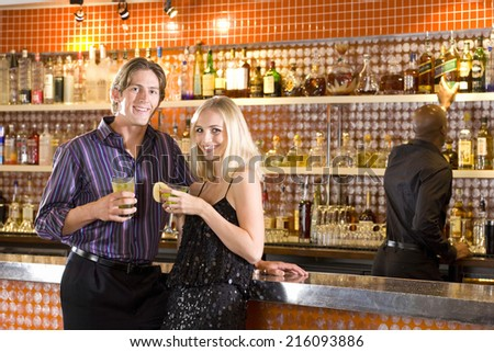 Young couple at bar with drinks, smiling, portrait - stock photo
