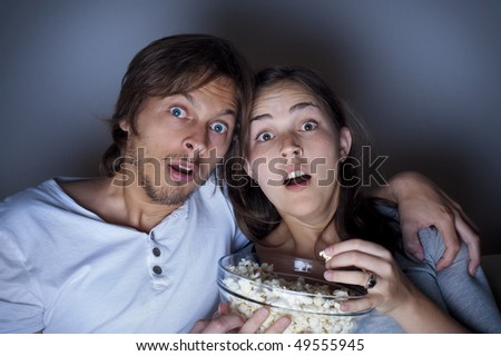 Young couple at home watching a movie with popcorn - stock photo