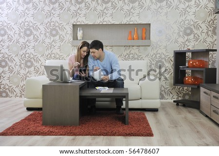 young couple at home with  modern livingroom indoor working on laptop on house finance and planing - stock photo