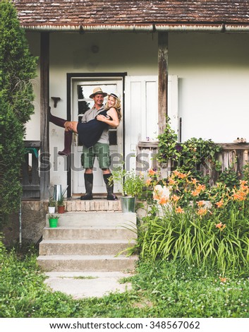 Young couple at new house front door, man holding his wife