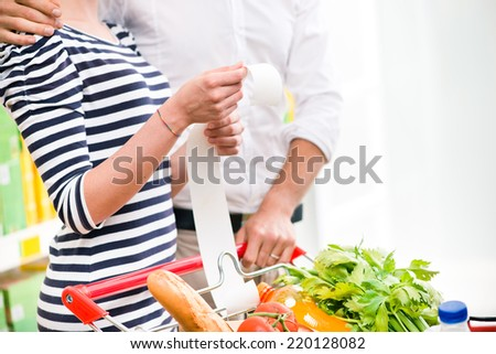 Young couple at supermarket checking a long receipt with shopping cart on foreground. - stock photo