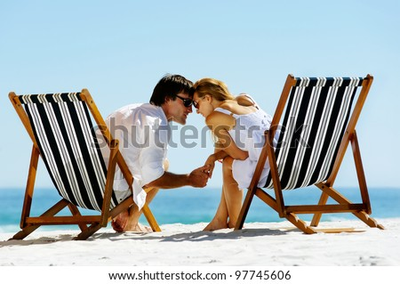 young couple at the beach in summer share an intimate moment of love and affection - stock photo