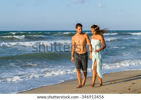 Young couple at the beach on a  hazy summer day at dusk, wearing a turquoise dress and shorts, enjoying  walking barefoot in the ocean water, getting wet, teasing and kissing one another.
