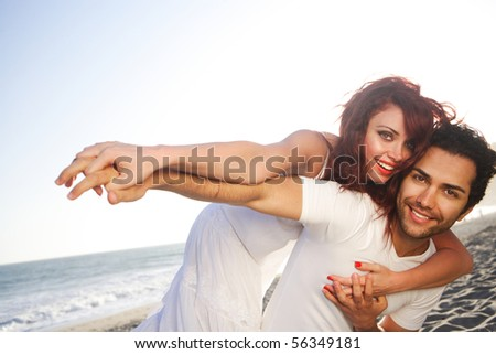Young couple at the beach posing - stock photo