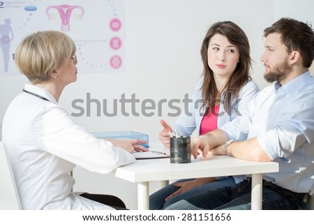 Young couple at the female doctors office - stock photo