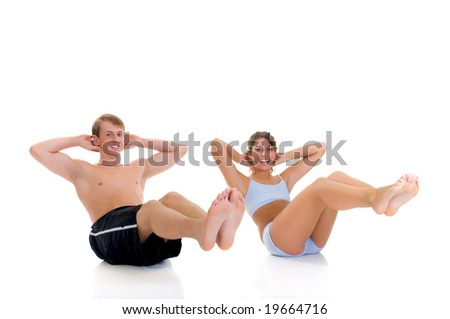 Young couple, attractive female, handsome male doing fitness exercises in the gym. Studio shot - stock photo