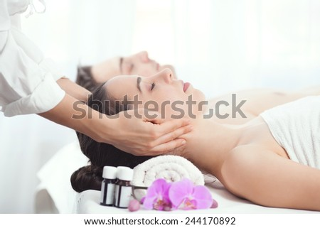 Young couple being massaged at the spa center - stock photo