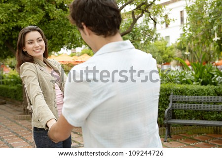 Young couple being playful in a park while on holidays in a Mediterranean destination. - stock photo