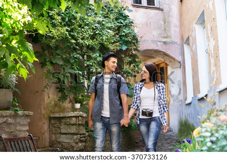 Young couple being tourists exploring an old town. - stock photo
