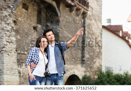 Young couple being tourists exploring the medieval buildings, - stock photo