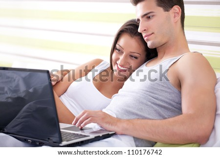 Young couple browsing the internet from their own bed.