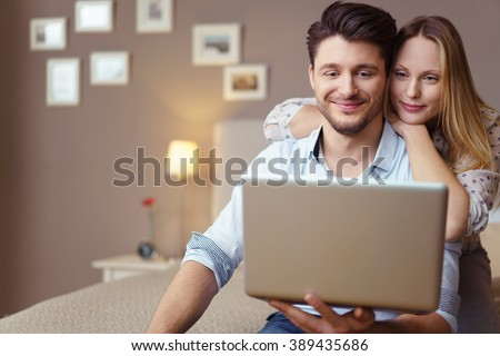 Young couple browsing the internet together sitting on a bed in a hotel room in a close embrace smiling happily as they read the screen