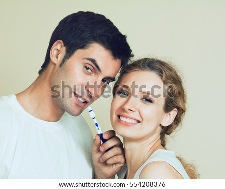 Young couple brushing teeth together at bathroom