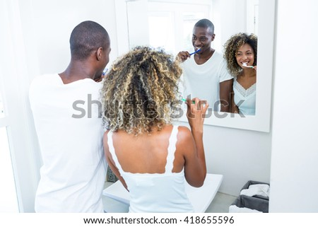 Young couple brushing their teeth at home in the bathroom - stock photo