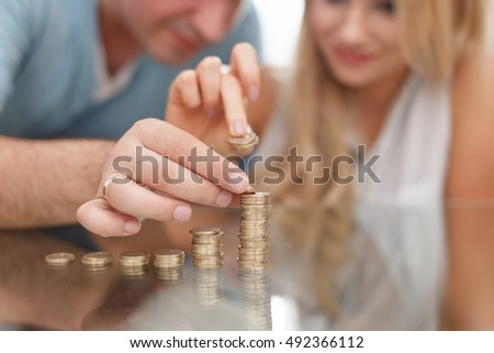 Young couple building coin columns on glass desk