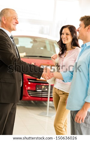 Young couple buying car from salesman shaking hands - stock photo