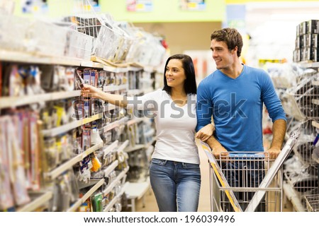 young couple buying padlock in hardware store - stock photo