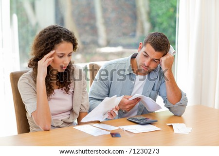 Young couple calculating their domestic bills at home - stock photo