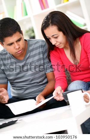young couple calculating their expenses in the living room - stock photo