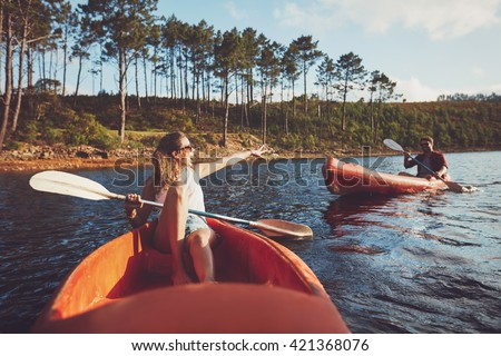 Young couple canoeing on the lake. Young kayakers enjoying a day at the lake. - stock photo