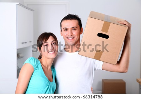 Young couple carrying boxes into new house - stock photo