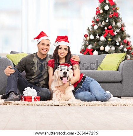 Young couple celebrating Christmas with their dog seated on the floor next to a modern gray sofa at their home - stock photo
