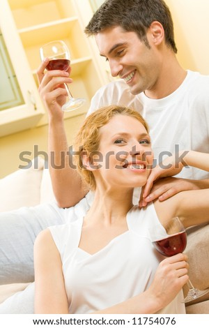 Young couple celebrating with red wine at home