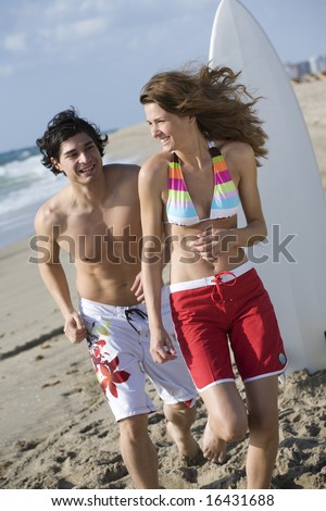 Young couple chasing each other on the beach
