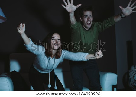 Young couple cheering for a sport team watching sports on TV - stock photo