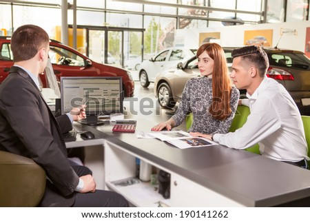 young couple chooses the car - stock photo