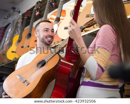 Young couple choosing acoustic guitar in music instruments store - stock photo