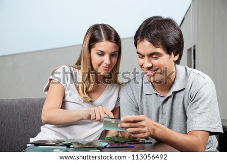 Young couple choosing between various glass tile swatches - stock photo