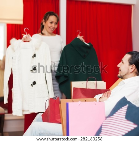 Young couple choosing coat in fitting-room at boutique