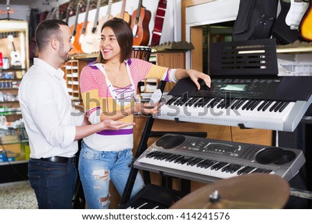 Young couple choosing synthesizer in music instruments shop - stock photo