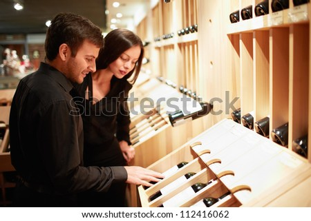 Young couple choosing wine in a store - stock photo