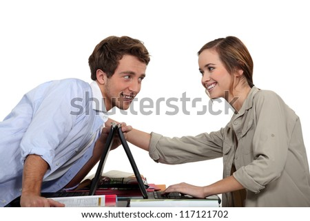 Young couple competing with laptops - stock photo