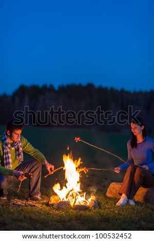 Young couple cook by campfire romantic night countryside - stock photo