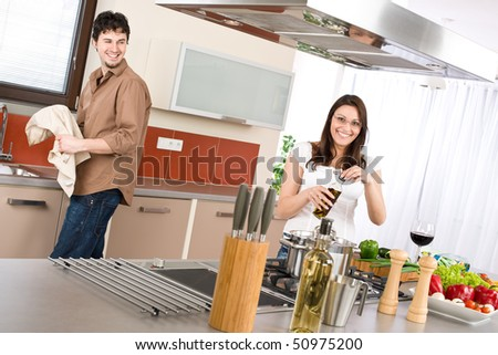 Young couple cook in modern kitchen, man helping with dishes - stock photo