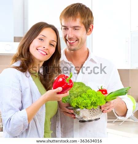 Young Couple Cooking Healthy food at home. Diet. Man and Woman in their Kitchen at home Preparing Dinner - Vegetable Salad. Dieting. Healthy vegetarian food, vegan. Family - stock photo