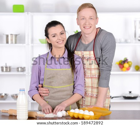 Young couple cooking in the kitchen in their homes - stock photo