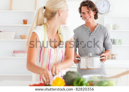 Young couple cooking in their kitchen - stock photo