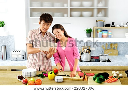 Young couple cooking - Men and women in the kitchen preparing food  - stock photo