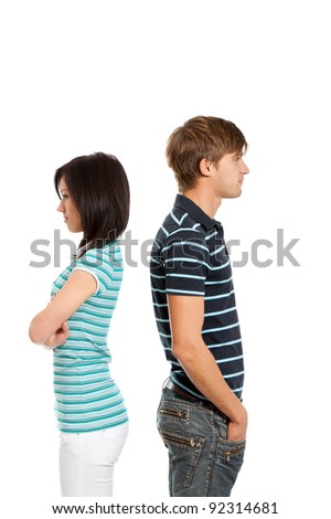 Young couple couple conflict concept, man and woman standing back to each other, isolated over white background - stock photo