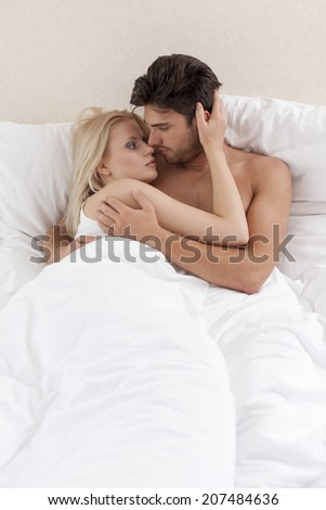 Young couple cuddling in bed - stock photo