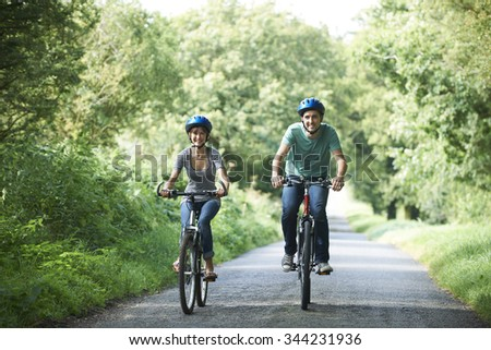 Young Couple Cycling Along Country Lane