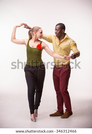 Young couple dances social Caribbean Salsa, studio shot  on white background. Positive human emotions. black african and Caucasian models - stock photo