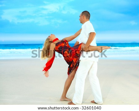 Young couple dancing on the tropical beach